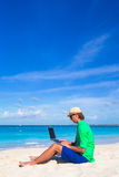 Young man working on laptop at tropical beach Royalty Free Stock Images