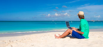 Young man working on laptop at tropical beach Stock Photos