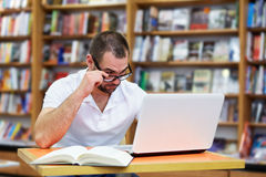 Young man working in a library Royalty Free Stock Photo
