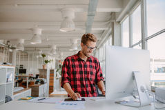Young man working in modern workplace Royalty Free Stock Images