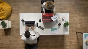 Young man working in office and giving document to female colleague, topshot, job concept overhead.  stock video footage