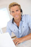 Young man working in office with headset Stock Photography