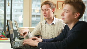 Young man working in the office of the laptops on the project. They confer on an important issue, and is shown in the. Two young man working in the office of the stock video footage