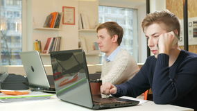 Young man working in the office of the laptops on the project. One is calling on the phone to the customer and records. Two young man working in the office of stock footage