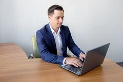Young man working in office, sitting at desk, looking at laptop computer screen. Stock Photo