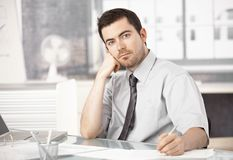 Young man working in office writing notes thinking stock photography