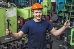 The young man working at the old factory on installation of equi. Pment in a protective helmet Stock Image