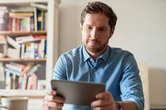 Young man working from home using a digital tablet. Young man working online with a digital tablet while sitting at a table in his living room Stock Photo