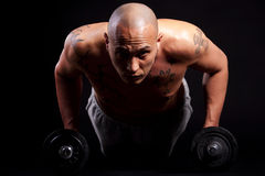 Young man working out. Young bald strong man is working out over black background Stock Photos