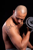 Young man working out. Young bald strong man is working out over black background Royalty Free Stock Image
