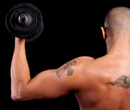 Young man working out. Young bald strong man is working out over black background Royalty Free Stock Images