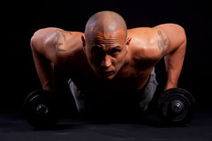 Young man working out. Young bald strong man is working out over black background Stock Images