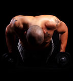 Young man working out. Young bald strong man is working out over black background Royalty Free Stock Photo
