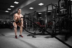 Young man working out with battle ropes Royalty Free Stock Photo