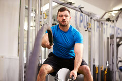 Young man working out with battle ropes at a gym Stock Image