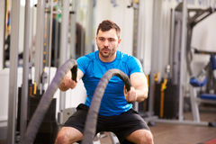 Young man working out with battle ropes at a gym Royalty Free Stock Photo