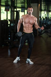 Young Man Working Out Biceps. Muscular Young Man Doing Heavy Weight Exercise For Biceps With Dumbbells In Modern Fitness Center Gym Stock Photography