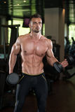 Young Man Working Out Biceps. Muscular Young Man Doing Heavy Weight Exercise For Biceps With Dumbbells In Modern Fitness Center Gym Stock Photo