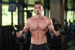 Young Man Working Out Biceps. Muscular Young Man Doing Heavy Weight Exercise For Biceps With Dumbbells In Modern Fitness Center Gym Royalty Free Stock Photos