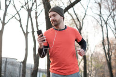 Young man working out in the city park and using his mobile phon. E Royalty Free Stock Image