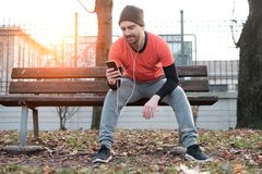 Young man working out in the city park and using his mobile phon. E Stock Photo