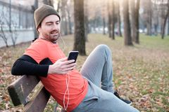 Young man working out in the city park and using his mobile phon Stock Photos