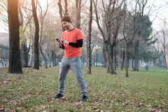 Young man working out in the city park. And using his mobile phone Royalty Free Stock Image