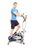 Young man working out on a cross trainer machine Royalty Free Stock Image