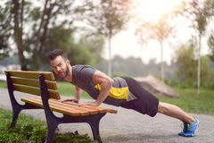 Young man working out doing push-ups. On a wooden park bench as he warms up for his daily workout or jog Royalty Free Stock Photography