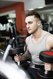 Young man working out with dumbbells. At fitness center Stock Image