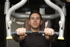 Young man working out on excerise machine Royalty Free Stock Photography