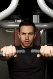 Young man working out on excerise machine Stock Images