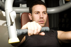 Young man working out on exercise machine Stock Photo