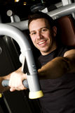 Young man working out on exercise machine Stock Photography