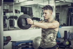 Young man working out in gym with kettlebells Stock Photos