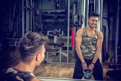 Young man working out in gym with kettlebells Royalty Free Stock Photography