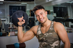 Young man working out in gym with kettlebells Stock Photo