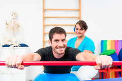 Young man working out in physical therapy on swiss ball with gym Stock Images