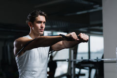 Young man working out with a resistance band in gym Royalty Free Stock Image