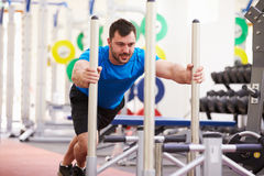Young man working out using equipment at a gym Stock Image