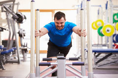 Young man working out using equipment at a gym Royalty Free Stock Image