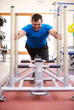 Young man working out using equipment at a gym, vertical Royalty Free Stock Photography