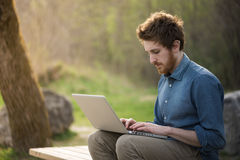 Young man working outdoors. Young hipster man working with his laptop outdoors in nature, trees and plants on background Stock Photography
