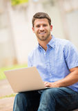 Young man working outside on laptop Stock Images