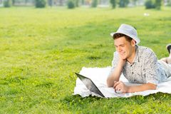 Young man working in the park with a laptop Royalty Free Stock Photography