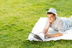 Young man working in the park with a laptop Royalty Free Stock Image