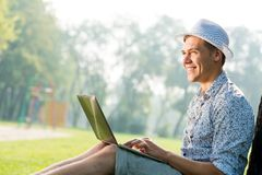 Young man working in the park with a laptop Royalty Free Stock Photos