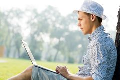 Young man working in the park with a laptop Stock Photo