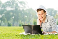 Young man working in the park with a laptop Stock Image