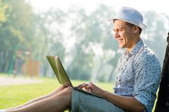 Young man working in the park with a laptop Stock Photos